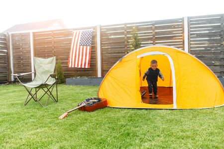 Father and son play camp in the backyard. A little toddler boy in an orange tent outdoors. Folding chair, guitar are near on the lawn