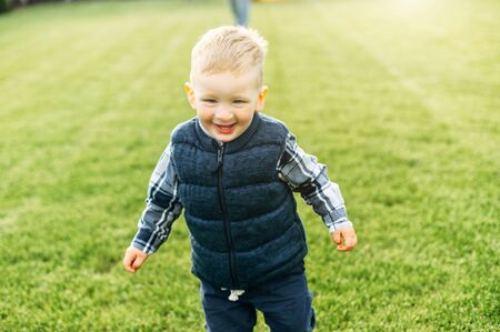 Laughing toddler boy is running on the green lawn outdoors. Happy childhood Standard-Bild
