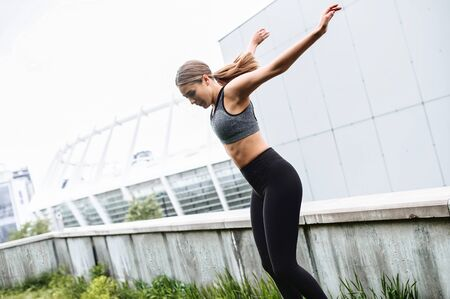Girl in sportswear is training on the street, she jumping. Outdoor Workout Concept