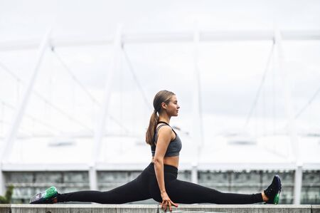 Flexibility training outdoors. A young beautiful flexible girl in trendy sports fit sits on the twine. Healthy lifestyle, stretching workout Standard-Bild