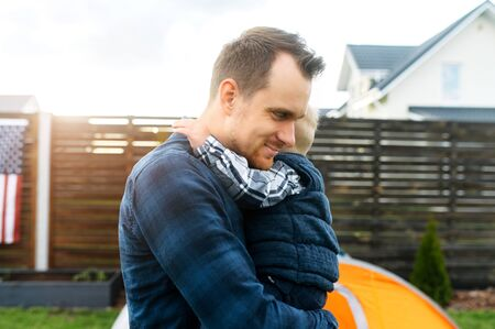 Father and son spend time together in the backyard. Cute baby boy hugs daddy Standard-Bild