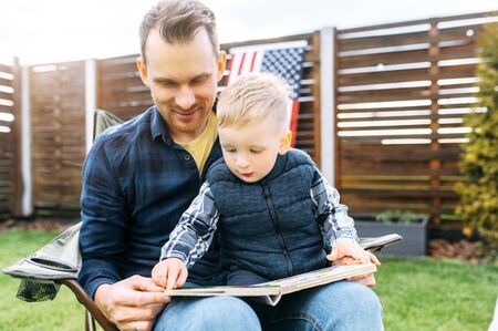Father and baby boy read a book outdoors. Dad spends time with son Standard-Bild