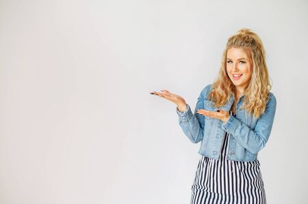 Just look at here. Beautiful blonde girl in casual wear points hands to empty space for text. Studio shot on white background Standard-Bild
