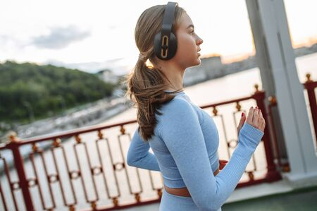 Pretty female jogger running and listening music in headphones outdoors on the city bridge road 免版税图像