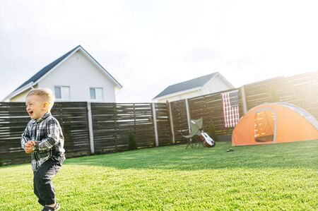 Dad and son have fun with a water in the backyard. A father is watering his toddler boy from hose, son runs away and laughs