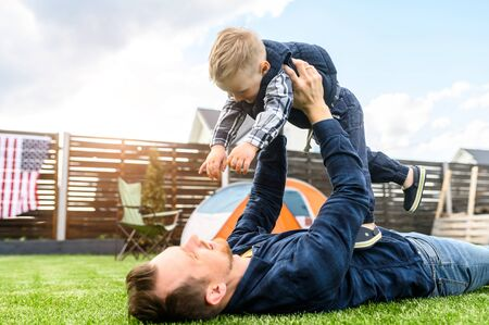 Young father and his cute toddler boy are laying on lawn, they play and laugh. Father and son have wonderful day together Standard-Bild