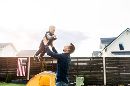 Backyard games. A young father is throws son up, american flag on a background Standard-Bild