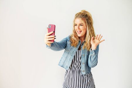 Cheerful young blonde woman using fancy smartphone for video call. Woman is striped dress stands and watches at selfie camera with a smile, white wall on background Standard-Bild