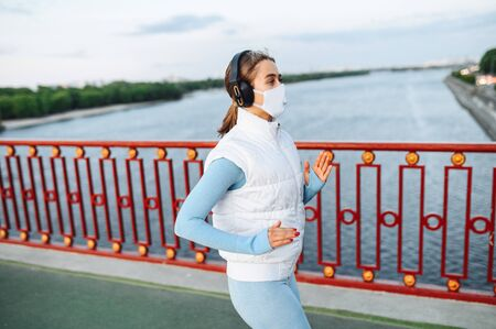 A girl with a protective mask on the face with headphones on her head is running on the city bridge road. Morning jog during quarantine Standard-Bild