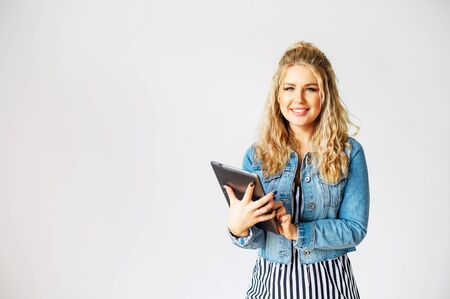 Young beautiful woman with a curly blonde hair is using tablet computer while standing with a white wall on background