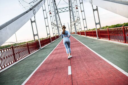 Back view of running girl. Young athlete woman is jogging on the pedestrian bridge. Outdoors run