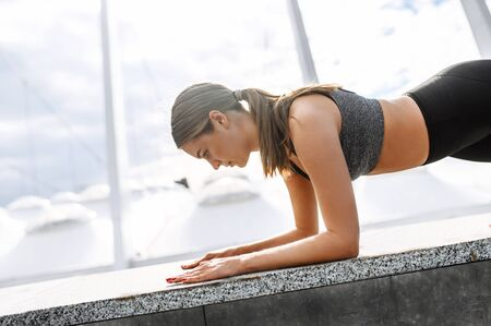 Close-up side view of beautiful athletic girl in sportswear, she is doing outdoors abs workout. A woman doing plank exercise perfect Standard-Bild