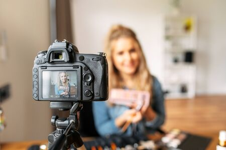 A young blonde woman talks about cosmetics and making a video for her beauty blog. Woman is holding a makeup palette and showing it at camera