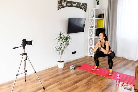 Recording fitness video tutorial at home. Attractive slender girl does exercises and records herself on camera. The concept of online classes, video tutorial Standard-Bild