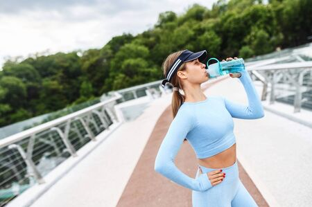 Beautiful athletic girl is drinking water after exercising outdoors. Thirst after running Standard-Bild
