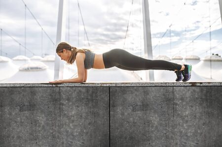 Get in shape yourself. Full length shot of attractive girl in sports outfit, she doing plank exercise outdoors. Self discipline and healthy lifestyle concept Standard-Bild
