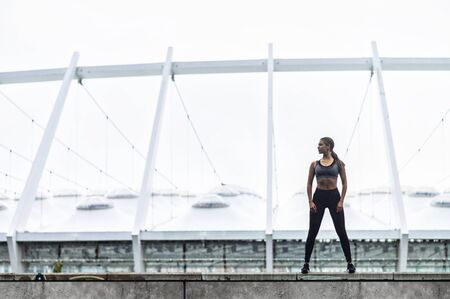 Keep your body in good shape. Slender young woman in sportswear stands in confident pose, a stadium on background