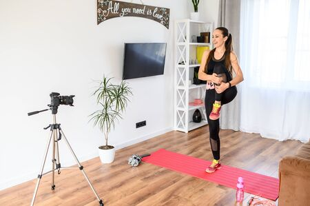 A young attractive fit woman is making video training, she is doing stretching exercises and recording herself on a camera. Online sports training at home Zdjęcie Seryjne