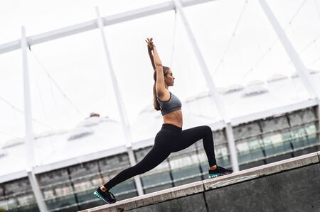 Beautiful athletic girl in sportswear practicing yoga outdoors. A woman doing high lunge. Healthy habits concept