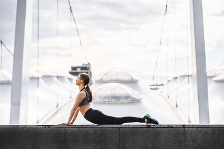 Outdoors yoga practicing. A young woman is practicing yoga on the roof top with a view on a stadium