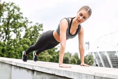 Beautiful and strong. A young athlete woman doing plank exercise outdoors. Stretching workout