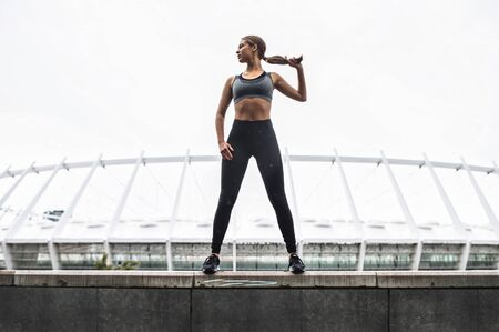 Beautiful strong and sporty young woman in sportswear stands in confident pose on the rooftop. Outdoors workout concept