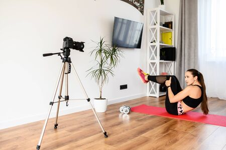 A girl in sportswear is recording workout at home video tutorial. An attractive young woman is doing her abs on the mat at home and records it on a video. Sports blogging, workout video tutorial