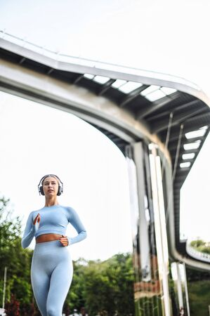 Morning jog. Young woman in sportswear runs among sityscape and listening music in headphones