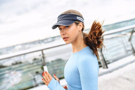 Morning jogging in the city. An athletic attractive woman in sportswear runs outdoors. Photo in motion. Self discipline and healthy lifestyle concept.