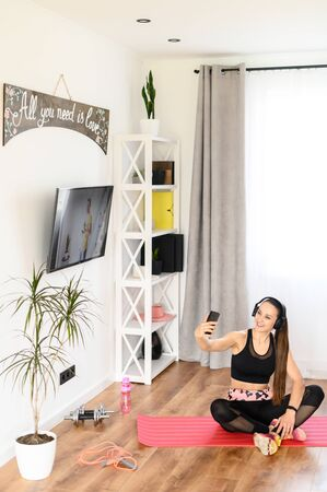 Selfie Time. Young woman in sportswear doing fitness at home. She takes a selfie on the phone and smiles. Standard-Bild