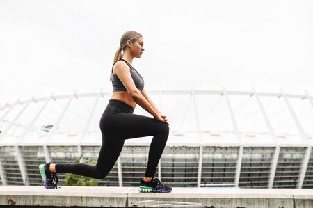 Female lower body workout. Slim and athletic girl doing lunges outdoors