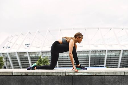 Female sports training outdoors. A girl in sports outfit doing lower body exercises