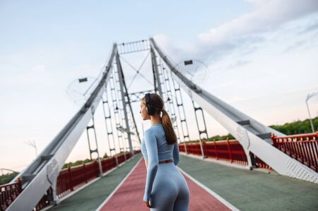 Healthy active lifestyle. Pretty athlete girl in trendy sports wear with a headphones on the city bridge in a sunset light