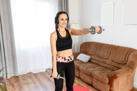 A young woman is doing strength-training workout with weights. A woman in sportswear training her arms and shoulders with a dumbbell at home