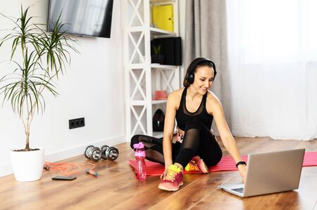 Beautiful woman in sportswear is watching workout videos on a laptop at home while taking a break between sets, she sits on the mat, dumbbells and jump rope are near on the floor