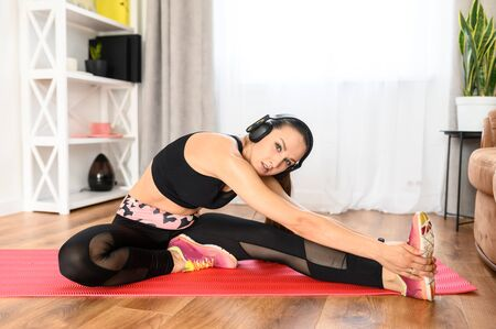 A young attractive woman is warming up before workout at home. She is stretching and listening music in headphones Standard-Bild