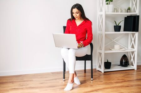 Working from home, brunette woman with a laptop on her knees. Young woman in red blouse working on a laptop computer sitting in a chair woth legs crossed. Banque d'images