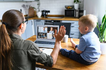 Mother work from home. Mom talks online, has video meeting, her toddler son sits near on looks at laptop