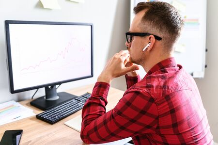 A young business man looks at the PC screen with graphs on it, he sits in the office with head leaning on his hands, wearing glasses, a view from his back