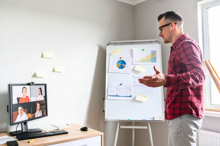 Confident young man conducts webinar, business training online. Online coach stands near flip chart in front of PC display and explains something to online audience