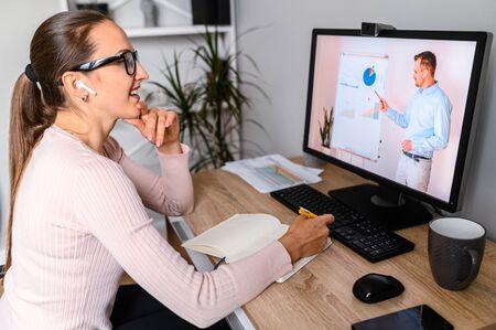 Webinaires, conférences en ligne. Une femme au bureau regarde des cours en ligne, un enseignant sur un écran d'ordinateur portable. Développement professionnel, formation commerciale
