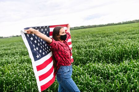 Young woman wearing black protective mask on her face stands with spread American flag among green field