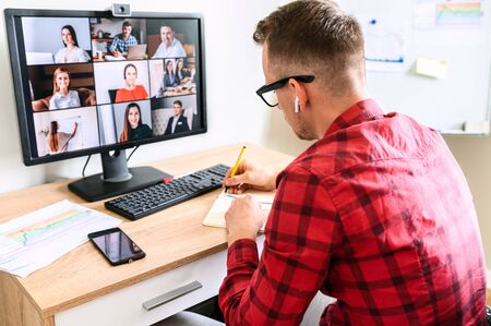 A young busy guy is making notes at the online conference video call with colleagues. He sits at the office desk, you can see his interlocutors on the PC screen