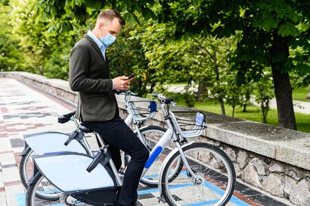 The guy gets to office without using public transport during pandemic. A young guy with medical mask in smart casual wear going to rent city bike, he is using app on the phone.