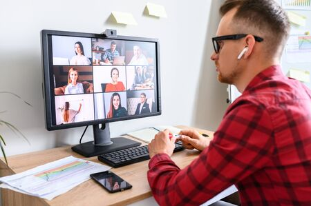 Online meeting of a young business man with his subordinates. A side back view of a young man talking via web camera to bunch of people at the workplace Foto de archivo
