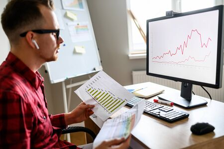 Concentrated guy lookolds printed s on the graph on PC monitor in front of him in the office and holds printed gistograms, he wears glasses and casual clothes, flipchart on background