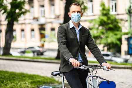 Young guy with a medical mask on the face in smart casual wear is riding a bicycle in the city. Precautions for epidemics, allergies, smog