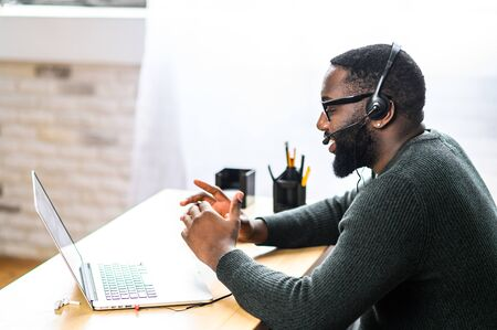 Concentrated young guy in smart casual wear and stylish glasses is using headset and laptop for online communication, supporting, selling. A black guy sits at the office desk, side view