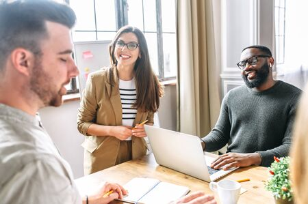 A friendly atmosphere in the office. Young, confident employees of the multiracial team discuss tasks and laugh at the morning meeting Stock Photo