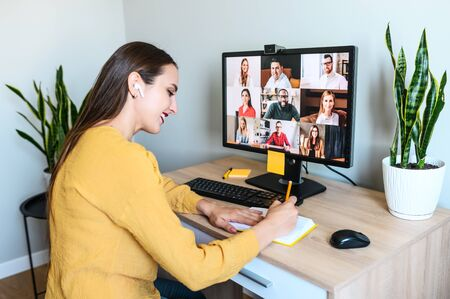 Virtual conference, morning meeting online. A young woman is using app on pc for connection with colleagues, employees, she is writing in notebook. Video call with many multiracial people togethe